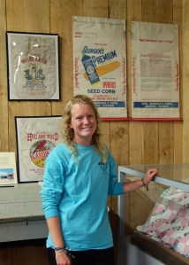 Emily in the Dubois County Museum standing under a Burger paper seed corn bag. Seed production and sales were part of the Burger farm business