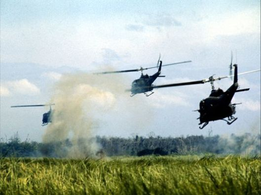 Huey lift platoon in Vietnam descending into landing zone to dispatch infantry troops.