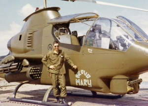 "Keith Cedras next to his Cobra gunship ""Proud Mary""."