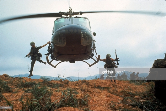 Troops jumping from Huey